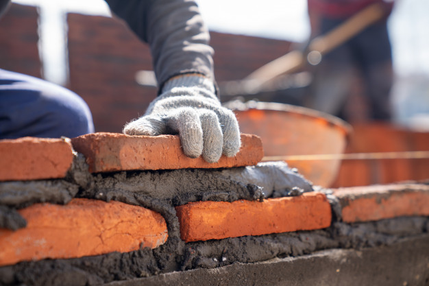 bricklayer-industrial-worker-installing-brick-masonry-with-trowel-putty-knife-construction-site